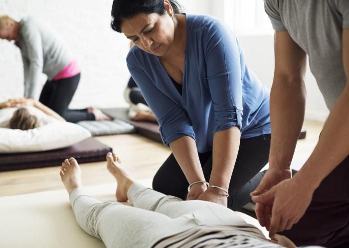Una alumna de un curso de masaje recibiendo instrucciones de su profesor.
