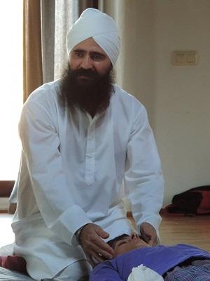 Lakhmi Chands Singh fundador de la primera escuela de Masaje Yoguico de Healing Hands en Europa. Aparece dando un masaje a una persona tumbada dentro de un espaico meditativo en un curso de masaje yóguico en Almeria.